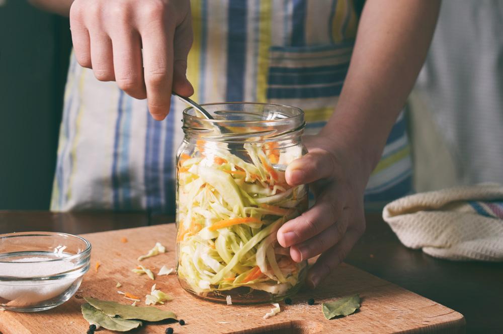 Gemüse wird in ein Glas gepackt, um es zu fermentieren