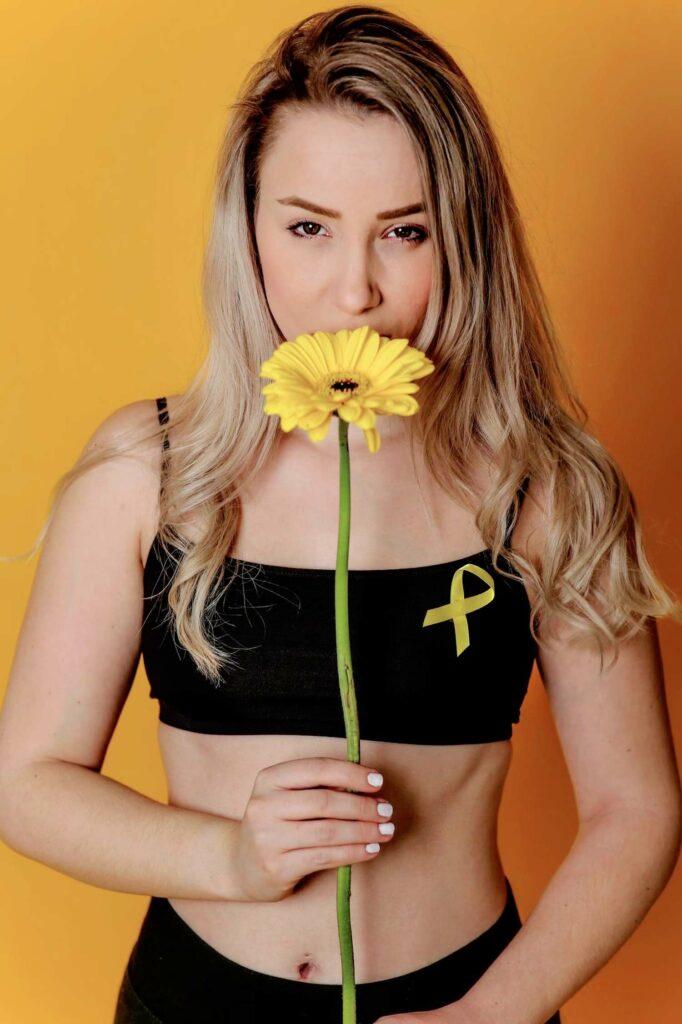 Melanie Vogt mit Sonnenblume und gelber Schleife (Symbole der Endometriose-Awareness)