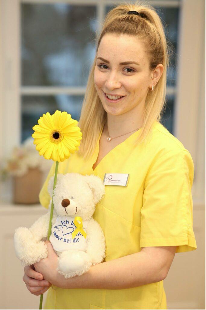 Melanie Vogt mit Teddy, Sonnenblume und gelber Schleife.