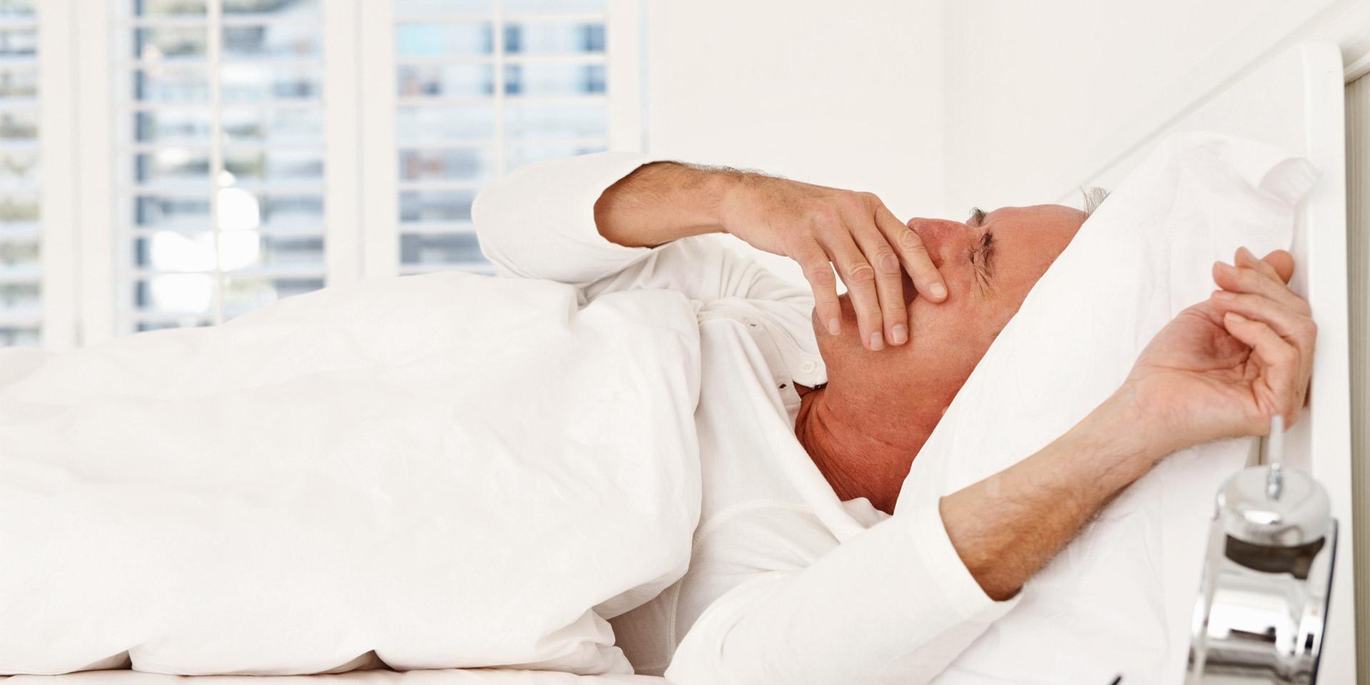 Älterer Mann liegt im Bett und schaut auf Wecker