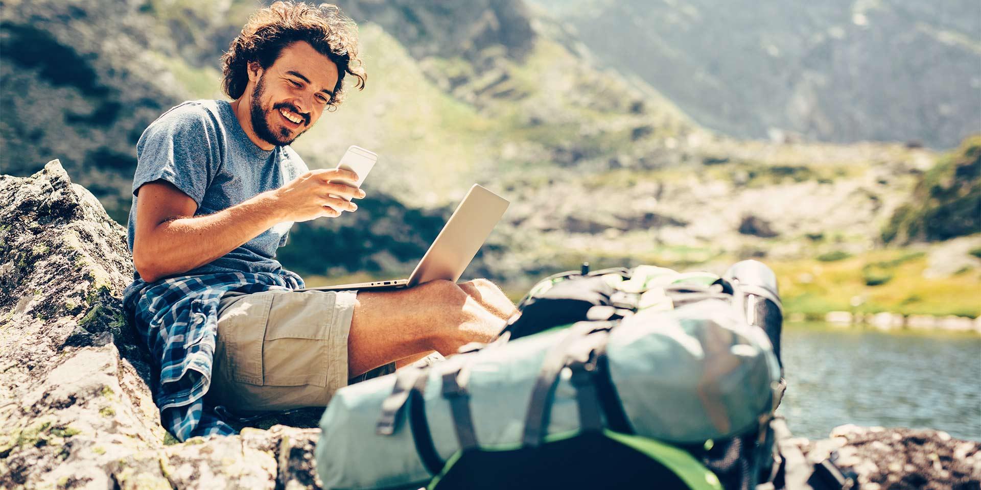 Junger Wanderer mit Smartphone und Laptop in der Natur
