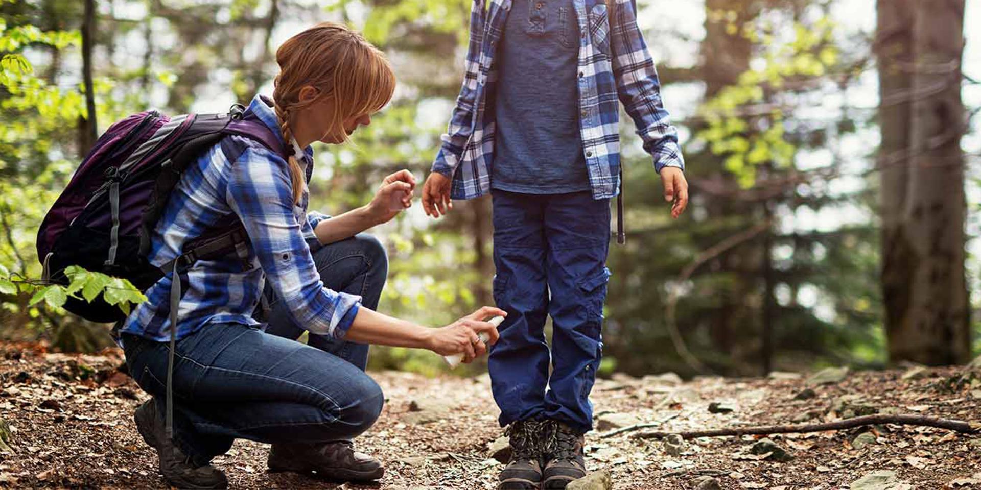 Mutter sprayt Sohn mit Zeckenspray ein